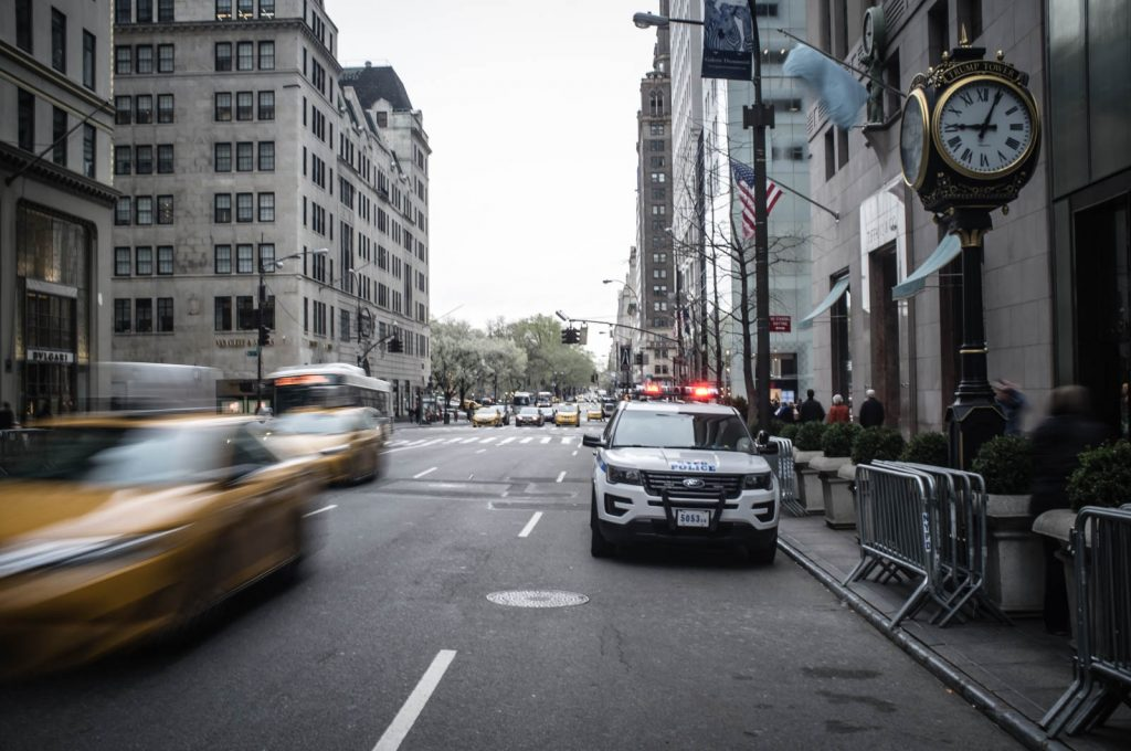 Taxis Speed by an NYPD 4x4 OUtside Trump Tower