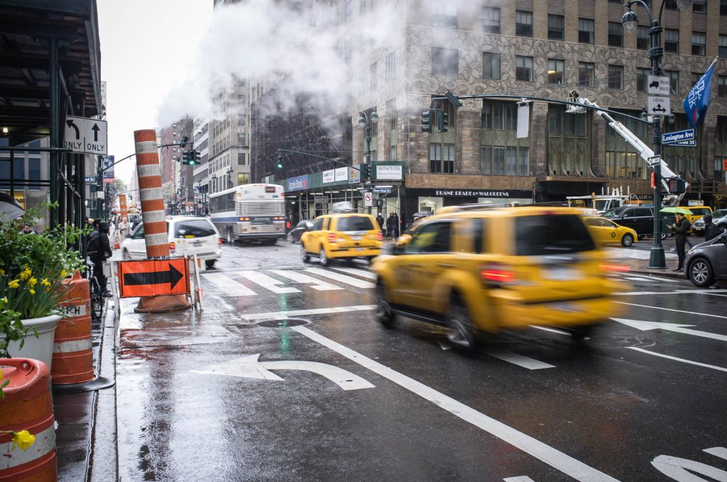New York Taxi Cabs speed past steam vents on Lexington Avenue, 9th April 2016