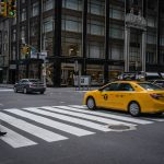 A pedestrian ignores the 'WAIT' sign on a crossing, as a Taxi Cab speeds across.